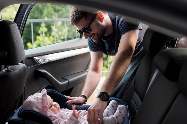 Erwachsener mann, der baby aus kindischem sicherheitssitz heraus nimmt