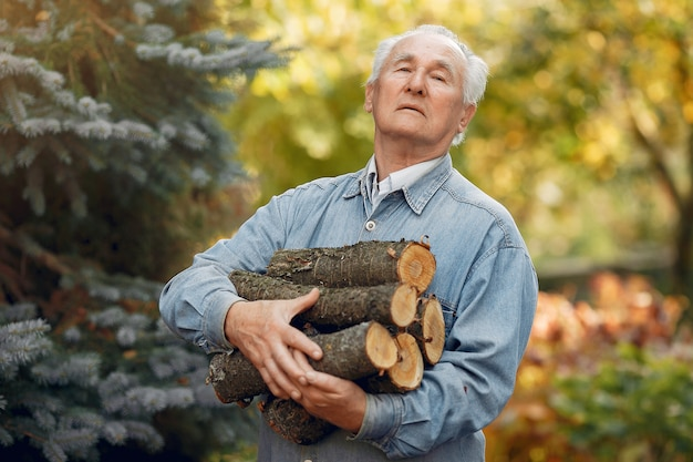 Erwachsener mann, der brennholz draußen hält
