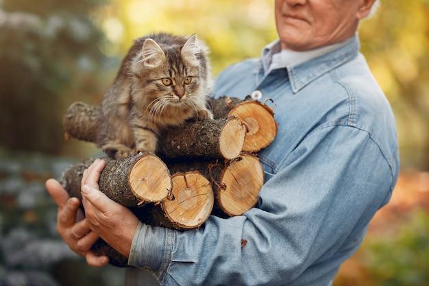 Erwachsener mann, der brennholz und eine katze hält