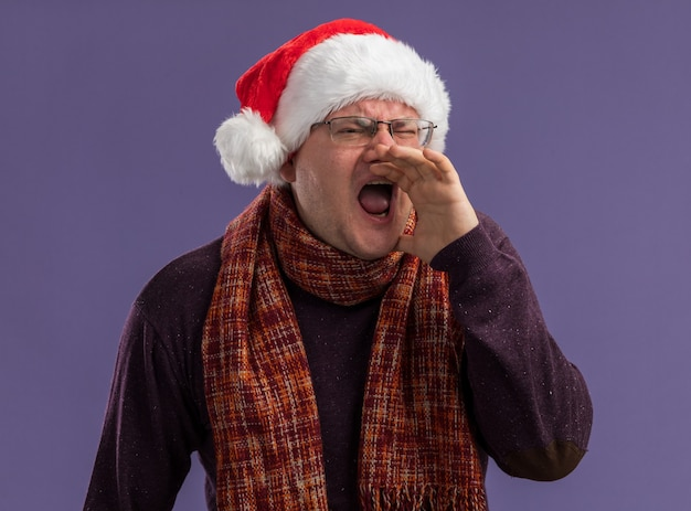 Erwachsener mann, der brille und weihnachtsmütze mit schal um den hals trägt hand in der nähe des mundes hält und seite betrachtet, die laut zu jemandem ruft, der auf lila hintergrund isoliert wird