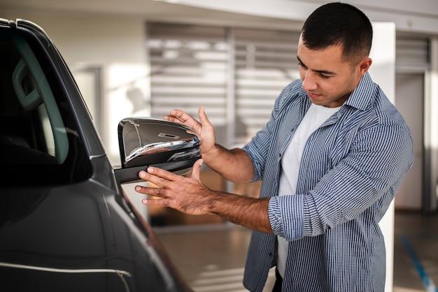 Erwachsener mann, der ein auto an der verkaufsstelle überprüft