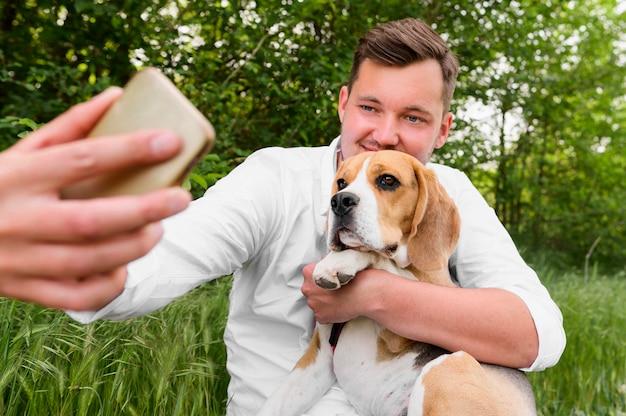 Erwachsener mann, der ein selfie mit hund nimmt