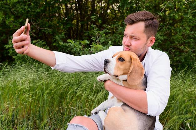 Erwachsener mann, der ein selfie mit niedlichem hund nimmt