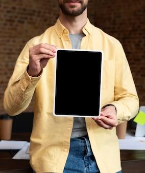 Erwachsener mann, der eine tablette im büro hält