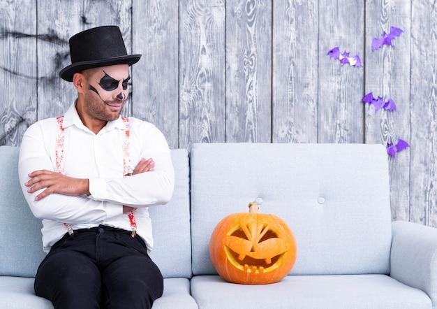 Erwachsener mann, der entlang des halloween-kürbises anstarrt