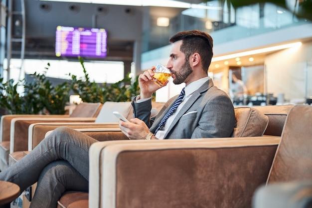 Erwachsener mann, der etwas whisky mit eis probiert, während er auf das telefon tippt