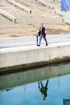 Erwachsener mann, der formelle kleidung beim gehen auf die promenade hält einen regenschirm trägt.