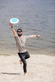 Erwachsener mann, der frisbee auf strand laufen lässt und fängt