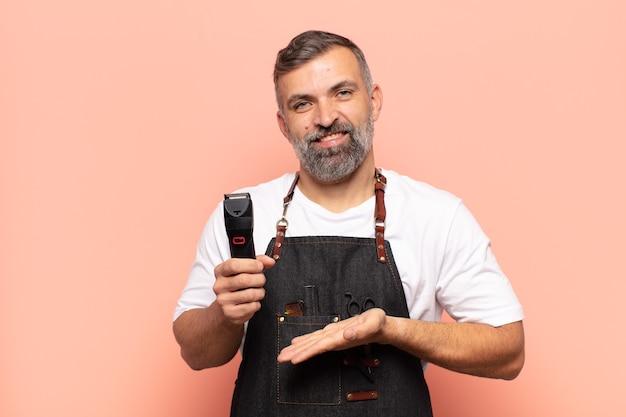 Erwachsener mann, der fröhlich lächelt, sich glücklich fühlt und einen elektrischen rasierer zeigt
