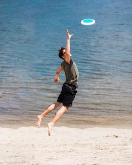 Erwachsener mann, der für anziehende frisbee-diskette springt