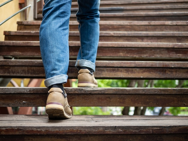 Erwachsener mann, der herauf die hölzerne treppe geht