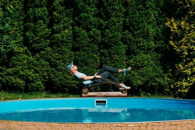 Erwachsener mann, der im liege über swimmingpool am landhaus in sizilien mit wand von grünen südlichen bäumen auf wand hinaus sich entspannt.