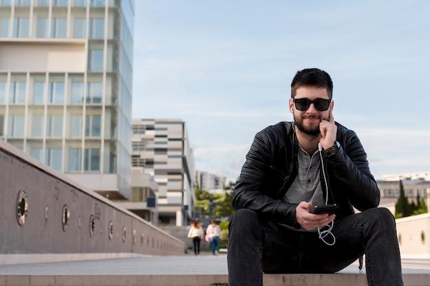 Erwachsener mann, der in der hand auf pflasterung mit smartphone sitzt