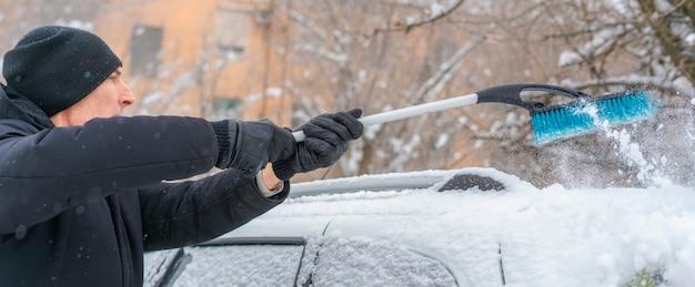 Erwachsener mann, der in der wintersaison mit einer bürste schnee vom autodach entfernt
