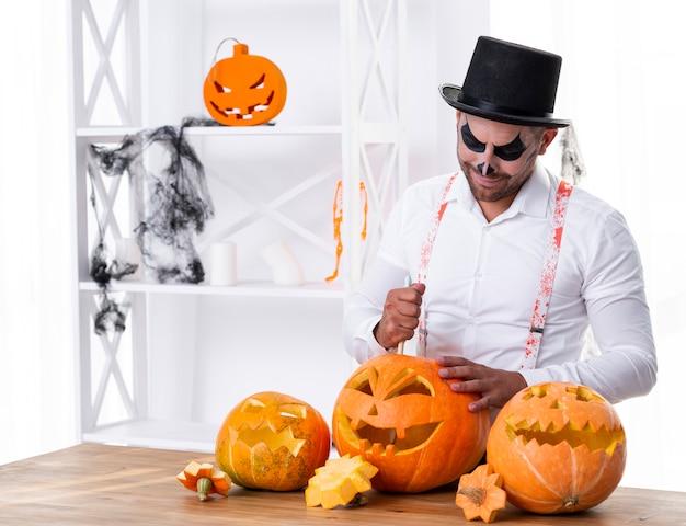Erwachsener mann, der kürbise für halloween schnitzt
