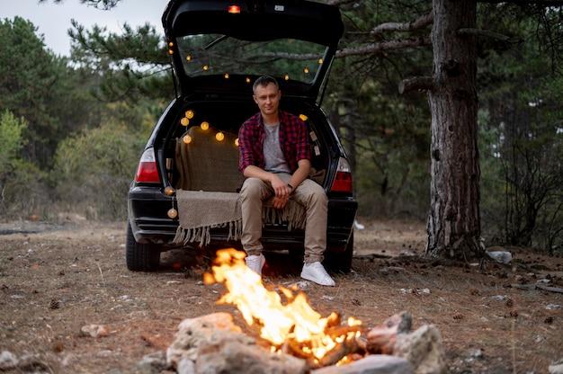 Erwachsener mann, der lagerfeuer genießt