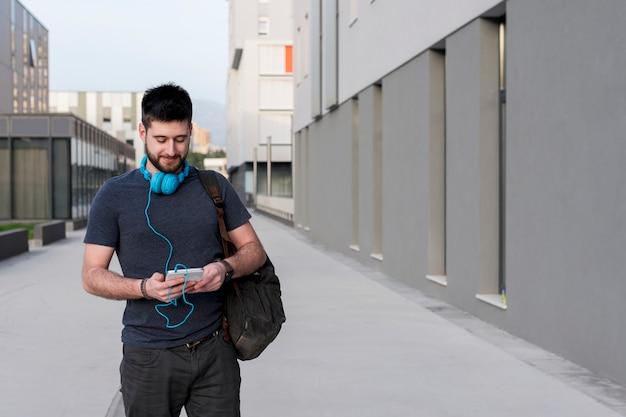 Erwachsener mann, der mit tablette und kopfhörern geht