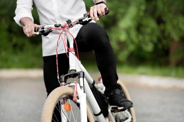 Erwachsener mann, der modernes fahrrad draußen reitet