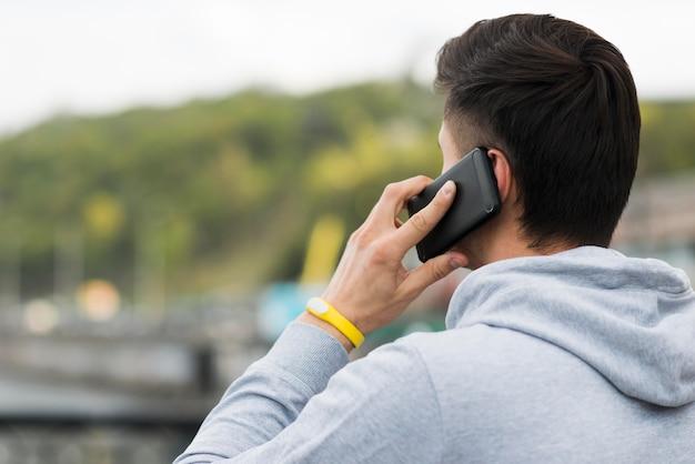 Erwachsener mann der nahaufnahme, der am telefon spricht