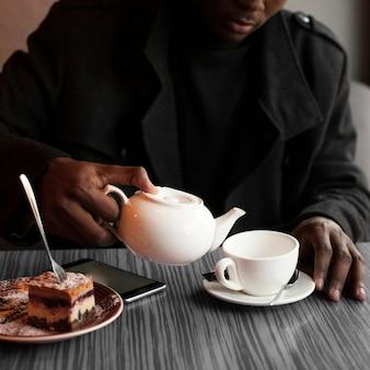 Erwachsener mann der nahaufnahme, der eine tasse tee genießt