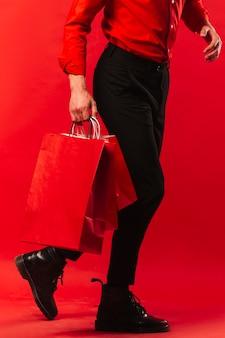 Erwachsener mann der nahaufnahme, der einkaufstaschen hält