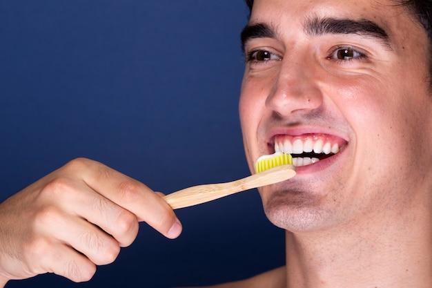 Erwachsener mann der nahaufnahme, der zahnbürste verwendet