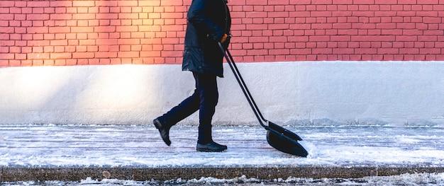 Erwachsener mann, der schnee von den straßen der stadt schaufelt