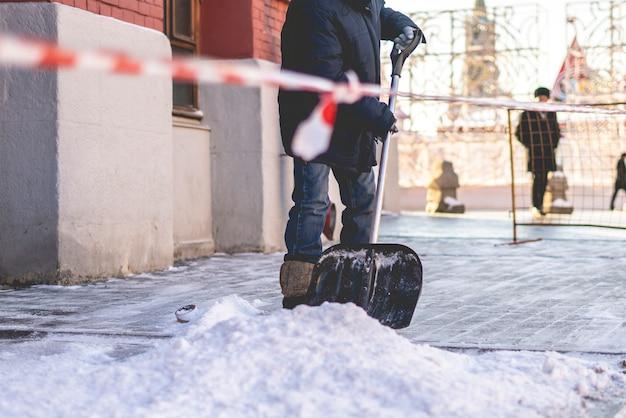 Erwachsener mann, der schnee von den straßen der stadt schaufelt Premium Fotos