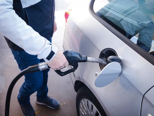 Erwachsener mann, der sein auto mit kraftstoff auffüllt.
