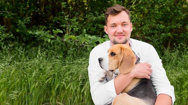 Erwachsener mann, der seinen entzückenden beagle hält