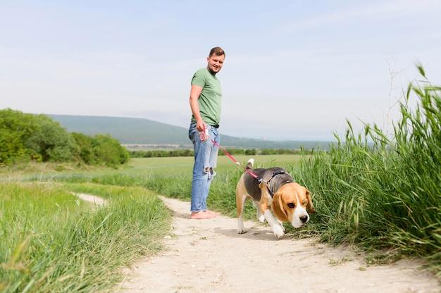 Erwachsener mann, der seinen hund für einen spaziergang nimmt