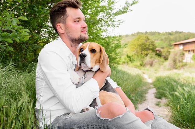 Erwachsener mann, der seinen hund im park hält