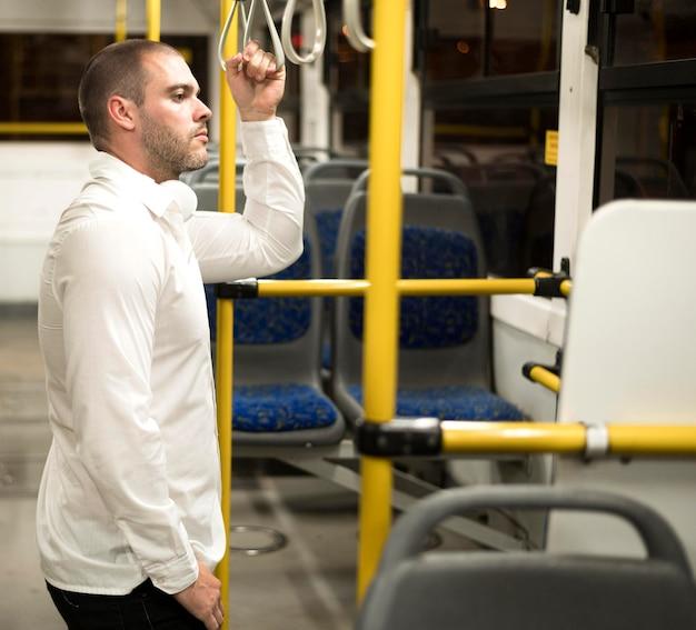 Erwachsener mann der seitenansicht, der den bus reitet