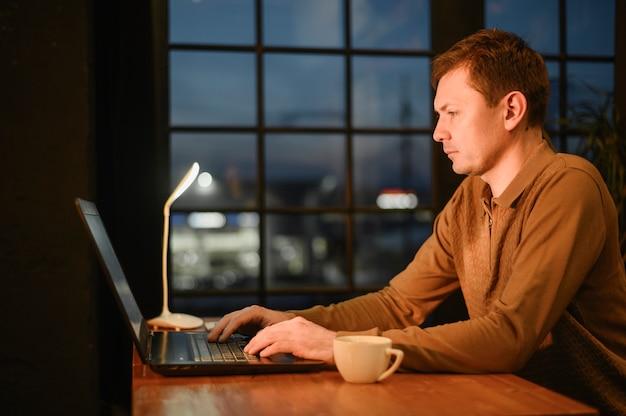 Erwachsener mann der seitenansicht, der entfernte arbeit genießt