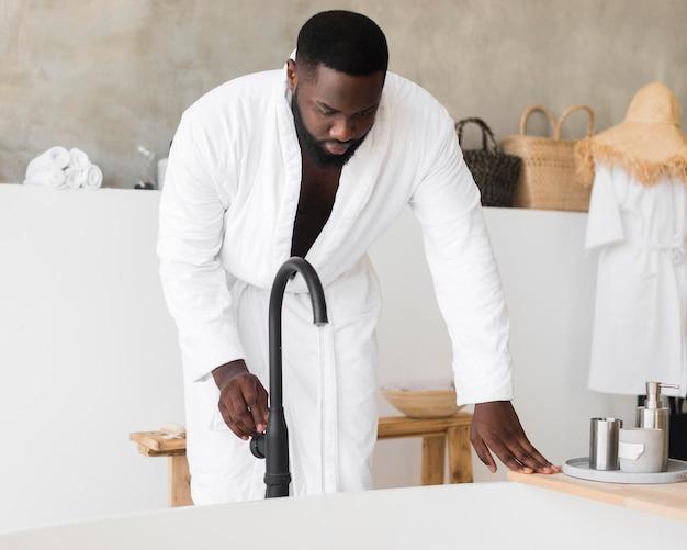 Erwachsener mann, der sich auf ein bad vorbereitet