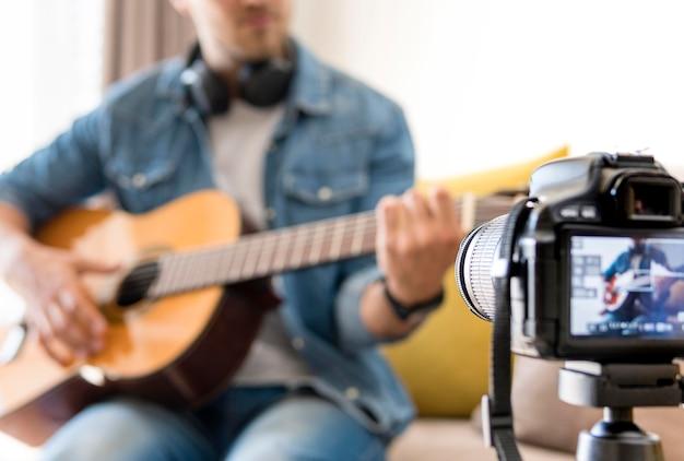 Erwachsener mann, der sich aufnimmt, während er gitarre spielt