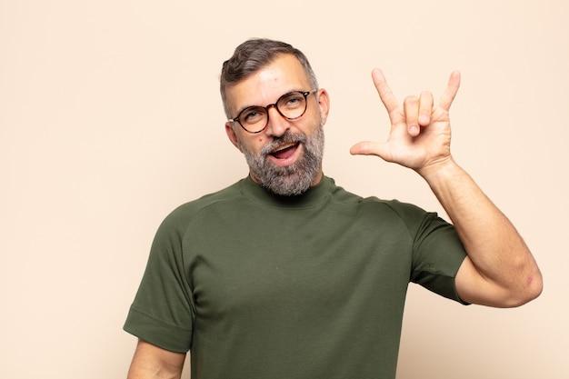 Erwachsener mann, der sich glücklich, lustig, selbstbewusst, positiv und rebellisch fühlt und mit der hand rock- oder heavy-metal-zeichen macht
