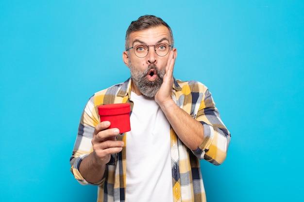 Erwachsener mann, der sich schockiert und verängstigt fühlt und mit offenem mund und händen auf den wangen erschrocken aussieht