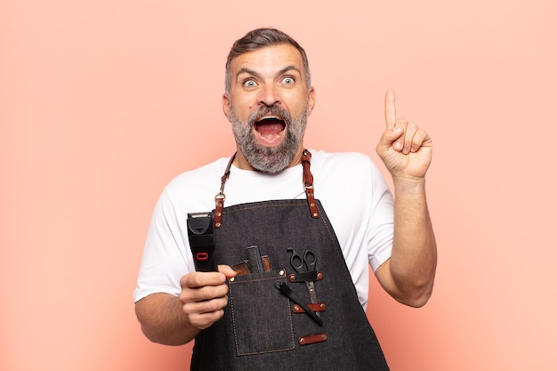 Erwachsener mann, der sich wie ein glückliches und aufgeregtes genie fühlt, nachdem er eine idee verwirklicht hat, fröhlich den finger hebend, eureka!