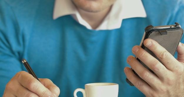 Erwachsener mann, der smartphone benutzt und kaffee trinkt