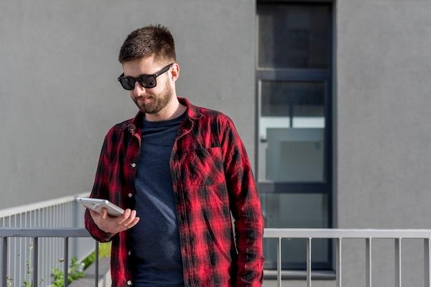 Erwachsener mann, der tablette draußen in der stadt verwendet