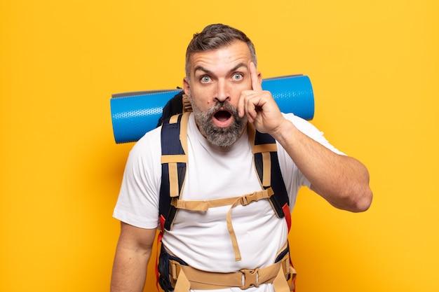 Erwachsener mann, der überrascht, mit offenem mund, schockiert aussieht und einen neuen gedanken, eine neue idee oder ein neues konzept verwirklicht