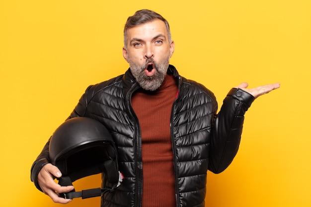 Erwachsener mann, der überrascht und schockiert aussieht, mit gesenktem kiefer, der einen gegenstand mit einer offenen hand auf der seite hält
