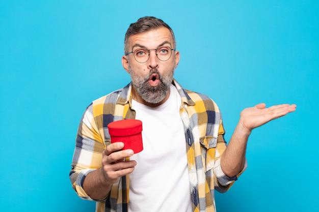 Erwachsener mann, der überrascht und schockiert aussieht, mit heruntergefallenem kiefer, der einen gegenstand mit einer offenen hand an der seite hält