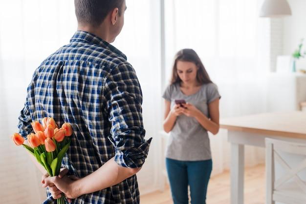 Erwachsener mann, der überraschung für frau mit telefon vorbereitet
