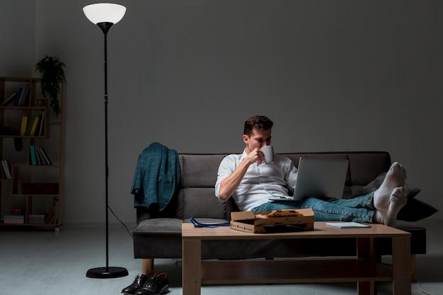 Erwachsener mann der vorderansicht, der eine pause von der arbeit macht