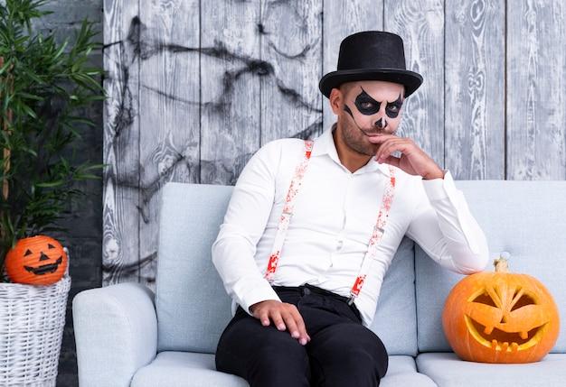 Erwachsener mann der vorderansicht, der für halloween aufwirft