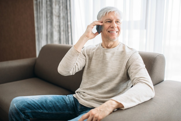 Erwachsener mann, der zu hause auf der couch sitzt und per handy spricht. reife männliche person in jeans entspannen im sessel