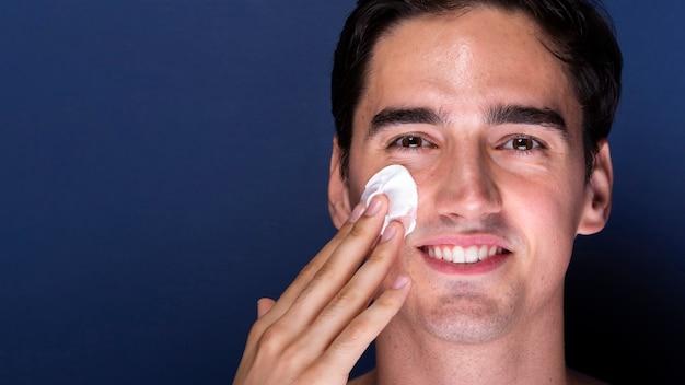 Erwachsener mann des smiley mit der anwendung des hautpflegeproduktes