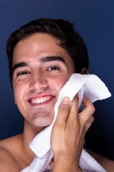 Erwachsener mann des smiley säubert gesicht